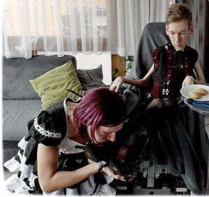Frau in Dienstmädchen Kleid kniet vor ihrem Herren im Rollstuhl und küsst seine Schuhe.