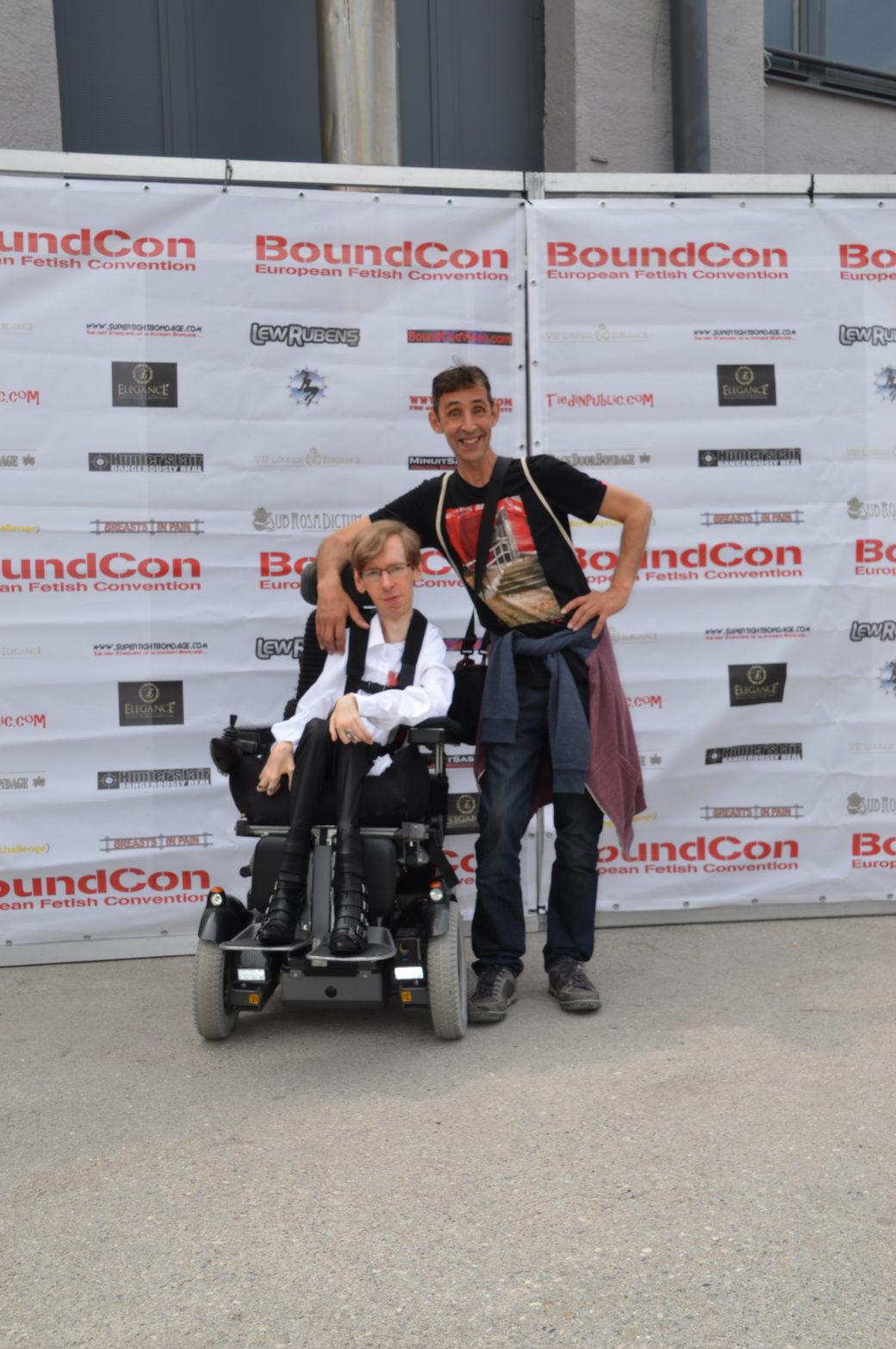Rollstuhlfahrer mit Freund vor dem Eingangsschild der Boundcon.