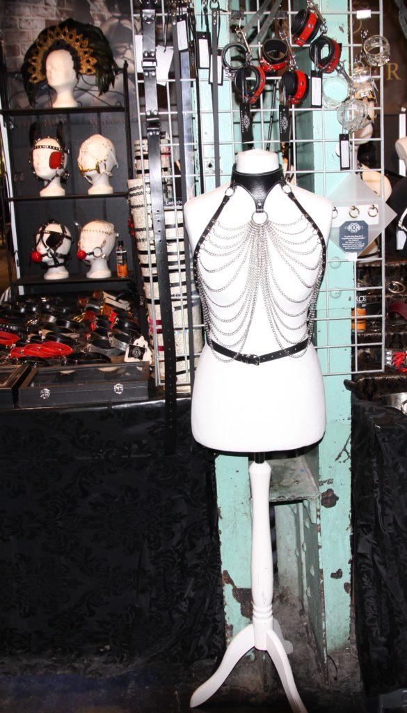 Dessous aus Leder und Ketten auf einem weiblichen Torso aus Plastik, im Hintergrund befinden sich Knebel, Fesseln und Halsbänder aus Ketten und Leder.