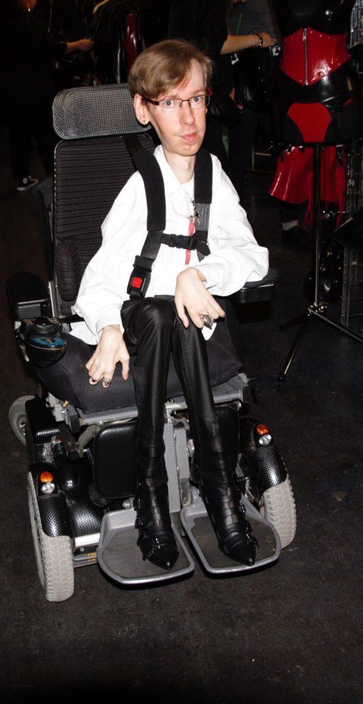 Rollstuhlfahrer auf der Boundcon neben einem Stand für Latex Kleidung.