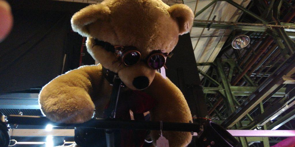 Ein großer Teddybär mit Fetisch Optik, unter anderem ein Halsband zur Fixierung der Arme.