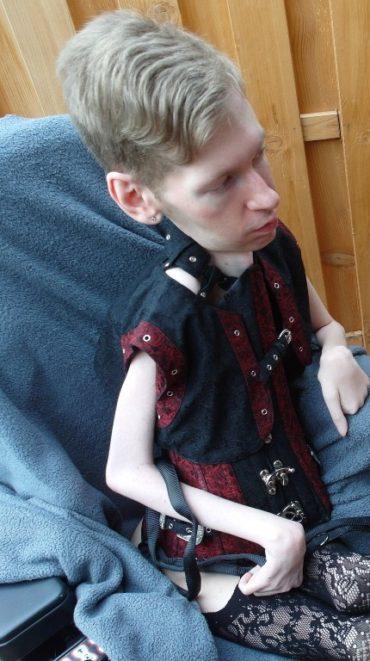 Behinderter Mann sitzt in einem rot schwarzen Korsett auf einer Terrasse.