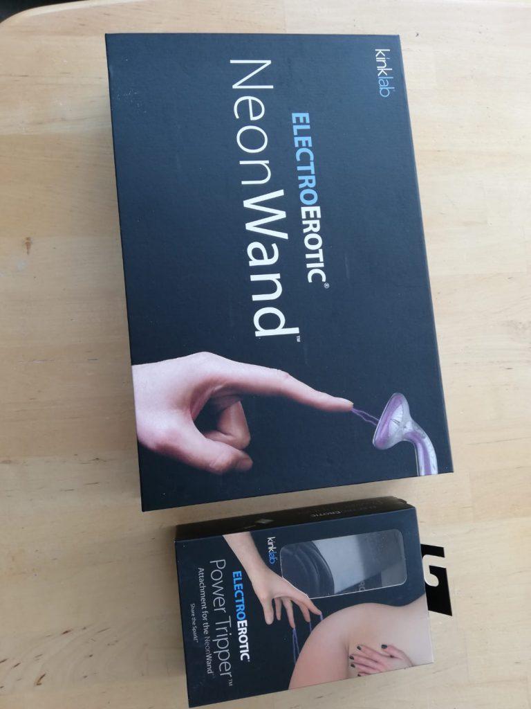 Sexspielzeug zur elektronischen Stimulation namens Neon Wand inklusive Zusatz Power Tripper in geschlossener Verpackung.