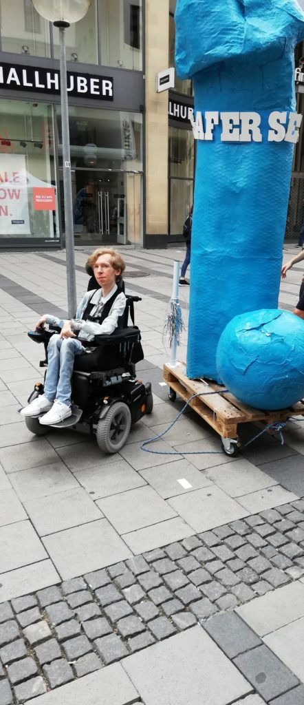 """Ein Rollstuhlfahrer steht neben einem 3 Meter hohen Plastik-Penis, der Penis trägt die Aufschrift """"Safer Sex"""""""