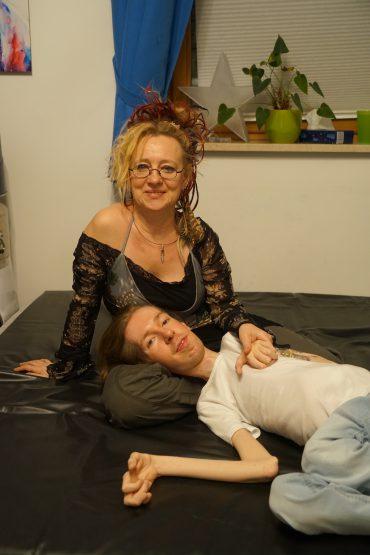 Die Sexualassistentin Deva Bhusha sitzt auf einem Bett, in ihrem Schoß ruht der Kopf ihres behinderten Partners. Beide Lächeln in die Kamera.