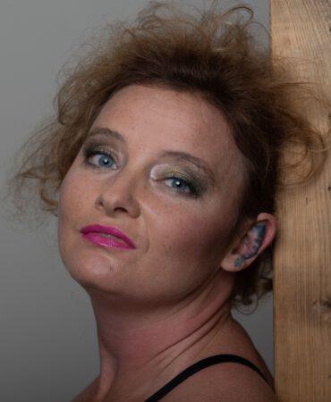 Die Sexarbeiterin Ruby lehnt an einer Holzwand. Den Kopf leicht nach Links geneigt blickt sie lasziv in die Kamera.