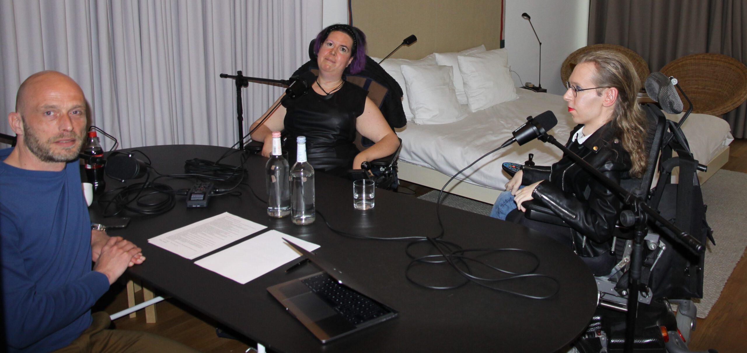 Andre, Jasmin und ich sitzen an einem ovalen schwarzen Tisch. Vor uns stehen die Mikrofone, gleich beginnt die Aufnahme für Heiß und Fetisch.