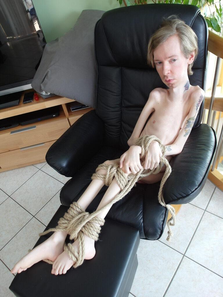 Ich sitze nackt auf einem schwarzen Sessel, meine Arme und Beine sind mit einem dicken Seil gefesselt. Mein Blick geht geistesabwesend in die Ferne. Es ist übrigens auch das Bild aus dem BDSM Magazin.